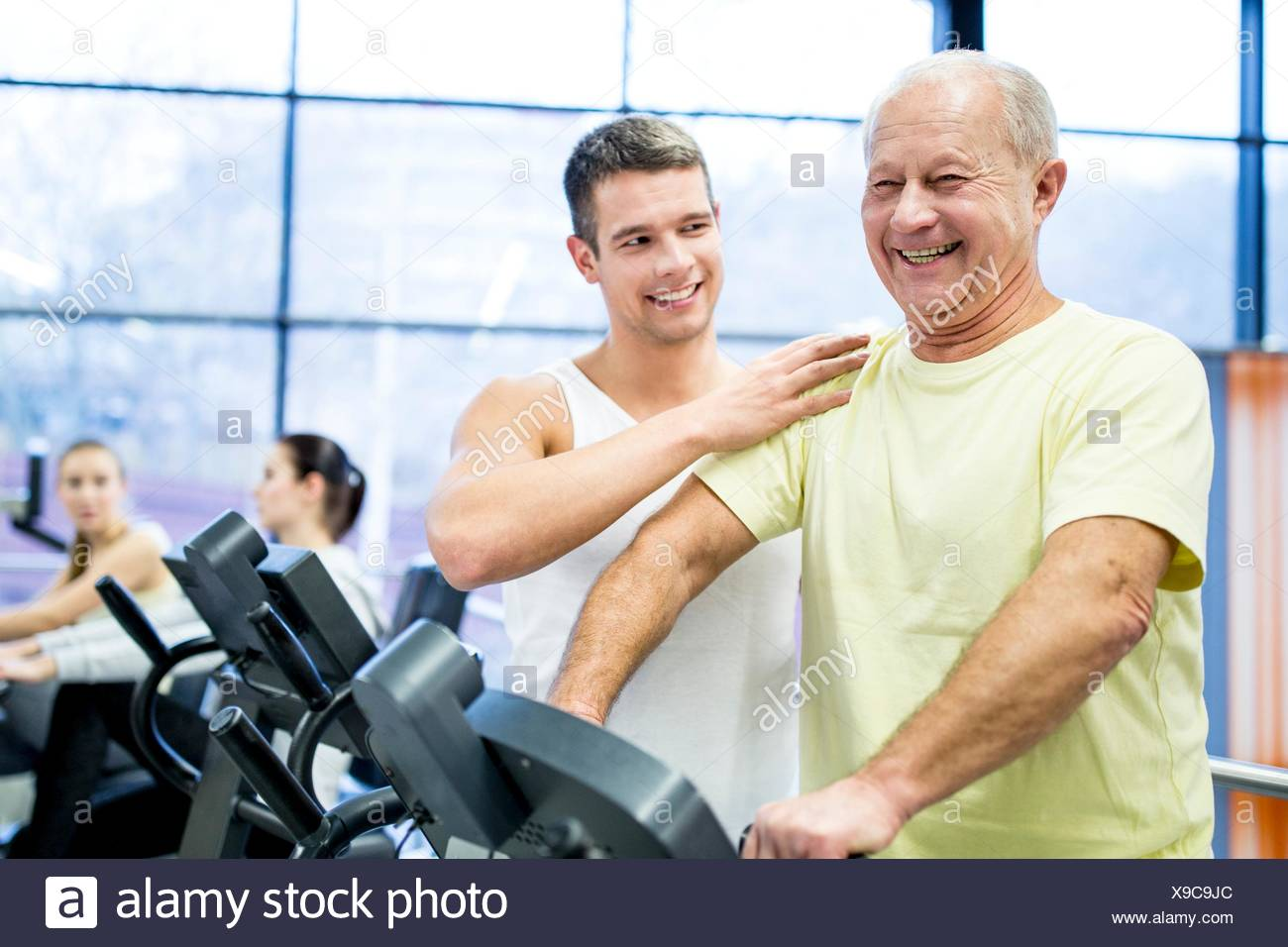 PROPERTY RELEASED. MODEL RELEASED. Young man assisting senior man while exercising on exercise bike in gym. - Stock Image