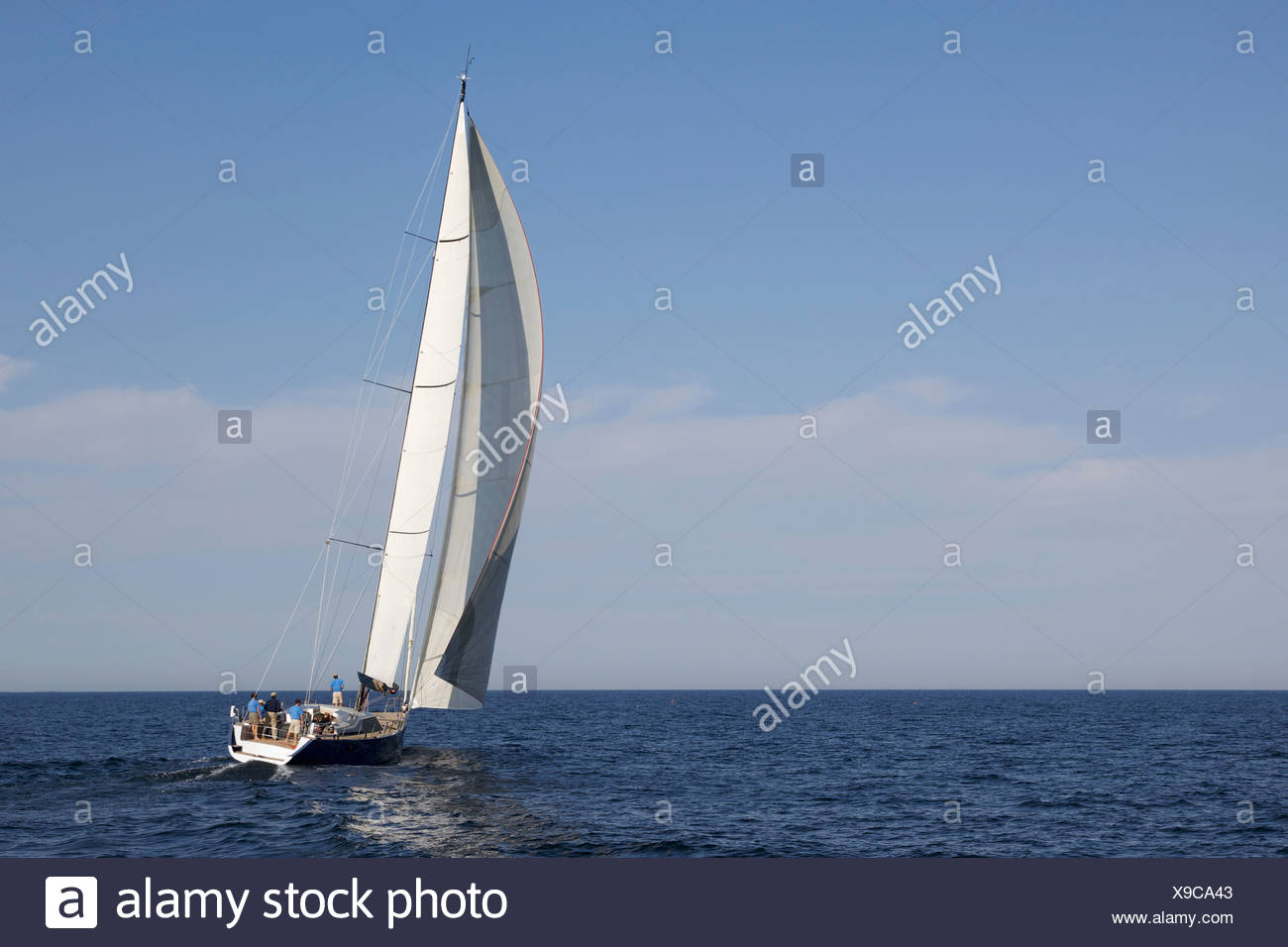 A crew races a modern ocean-going sailing yacht. - Stock Image