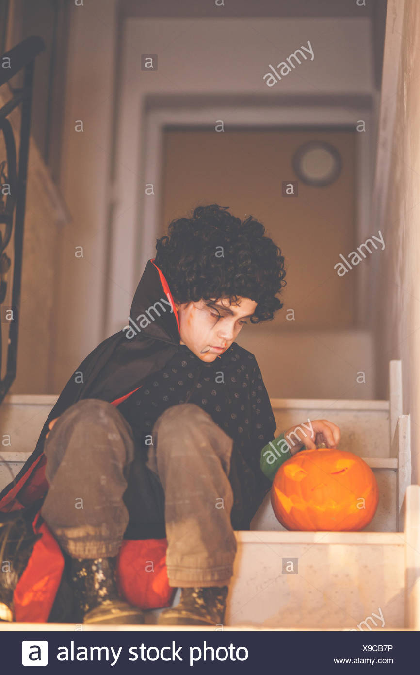 Boy in halloween dracula costume sitting on steps with a jack-o-lantern Stock Photo