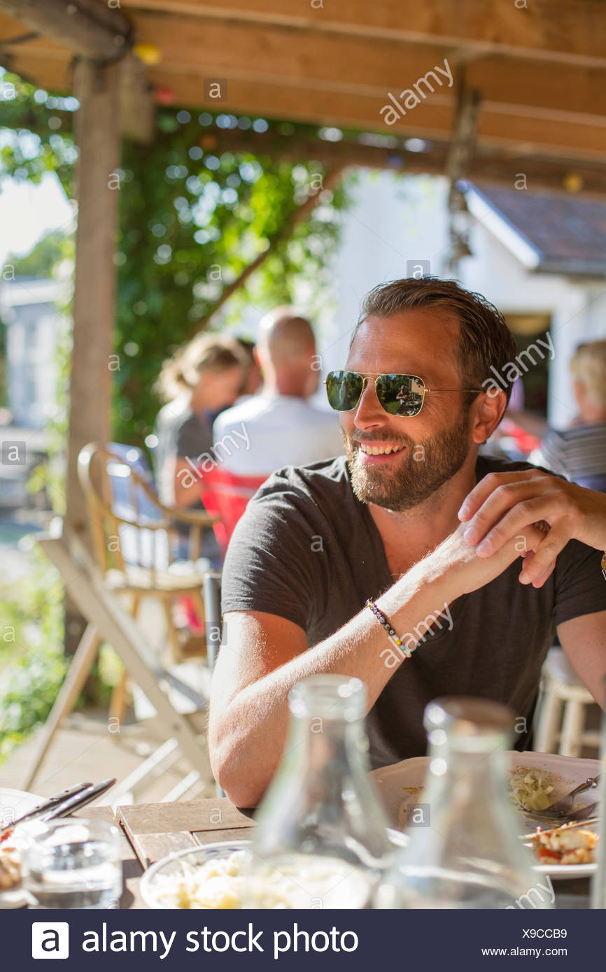 Sweden, Skane, Mature man in sunglasses eating lunch - Stock Image