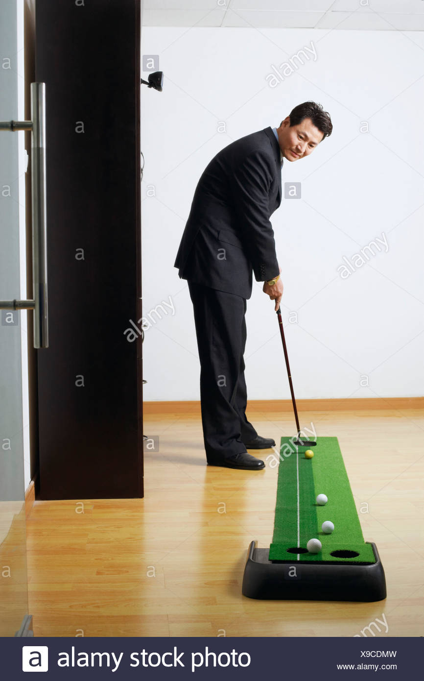 Side profile of a businessman practicing golf in a room - Stock Image