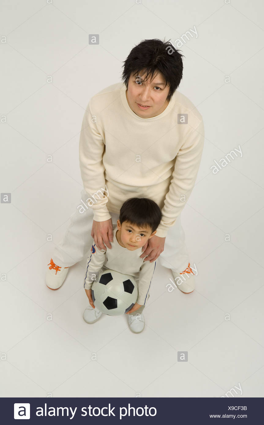 Father and son looking up at camera - Stock Image