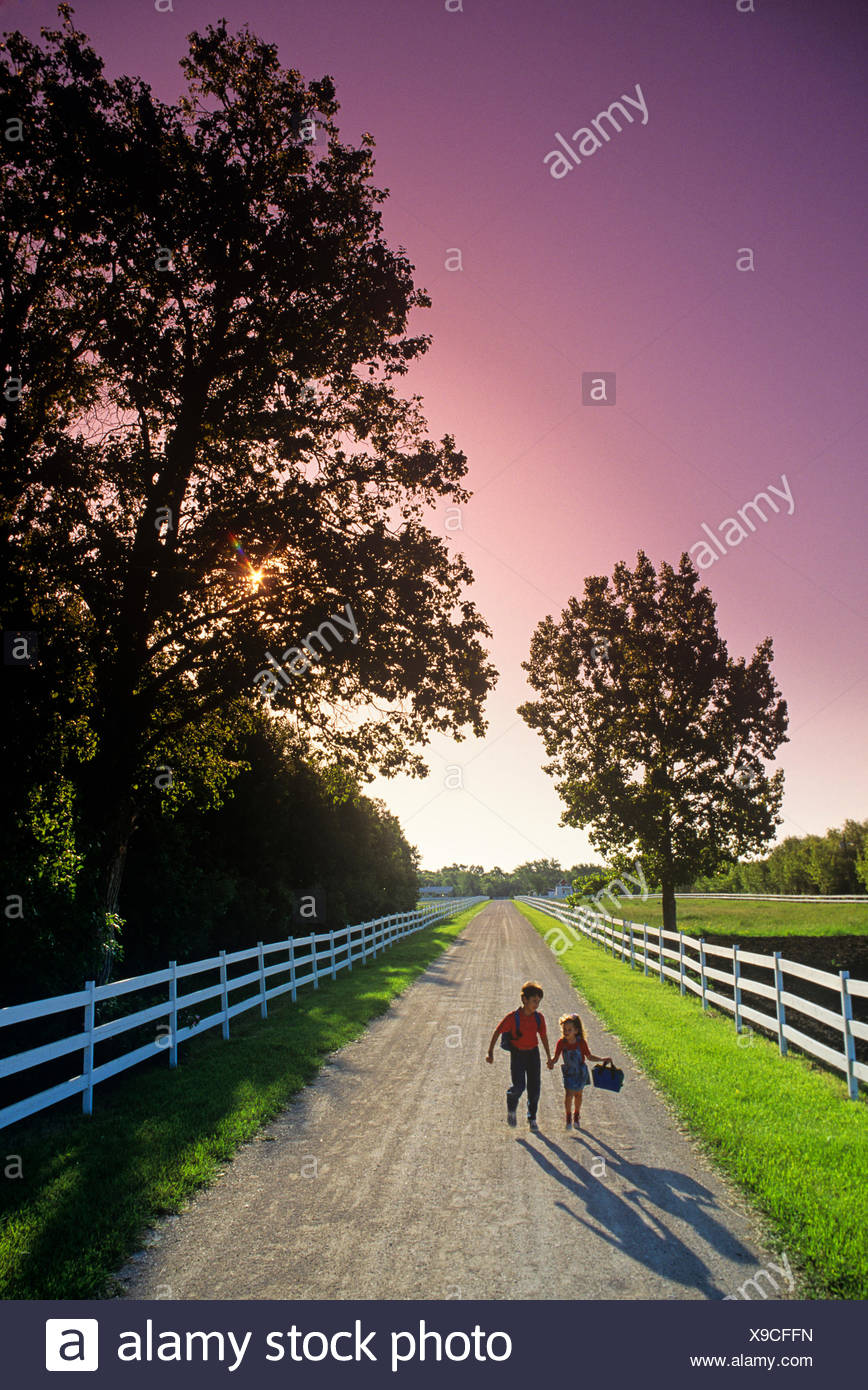 two childen run down a country road on their way to school, near Grande Pointe, Manitoba, Canada - Stock Image