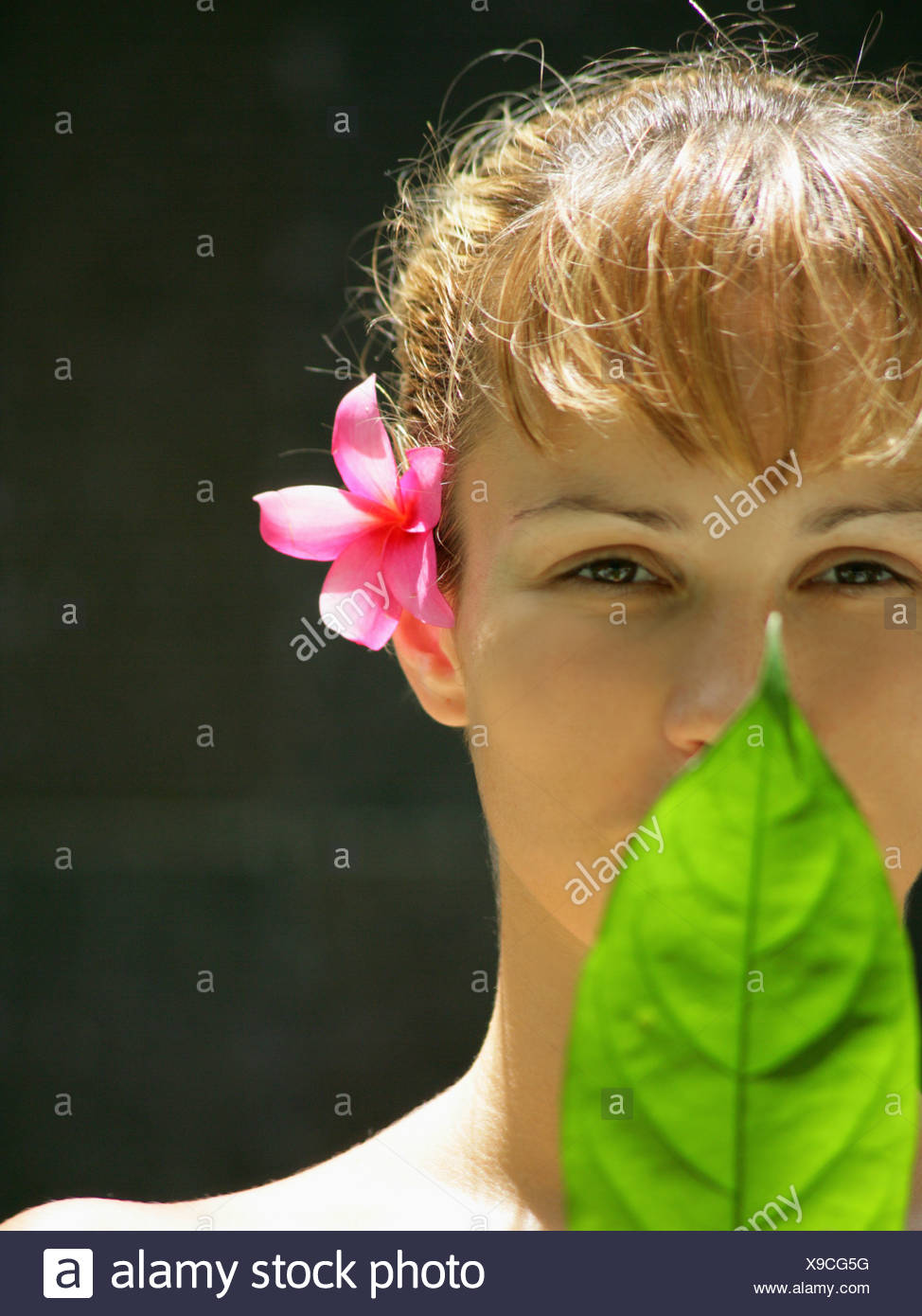 Close-up of a young woman holding a leaf in front of her face - Stock Image