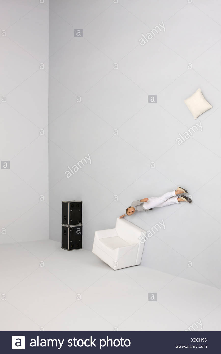 Woman floating midair, holding onto armchair, being blown away by sound from speakers - Stock Image
