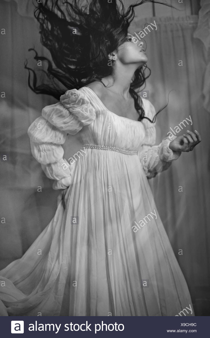 A young woman with long dark hair wearing a white dress - Stock Image