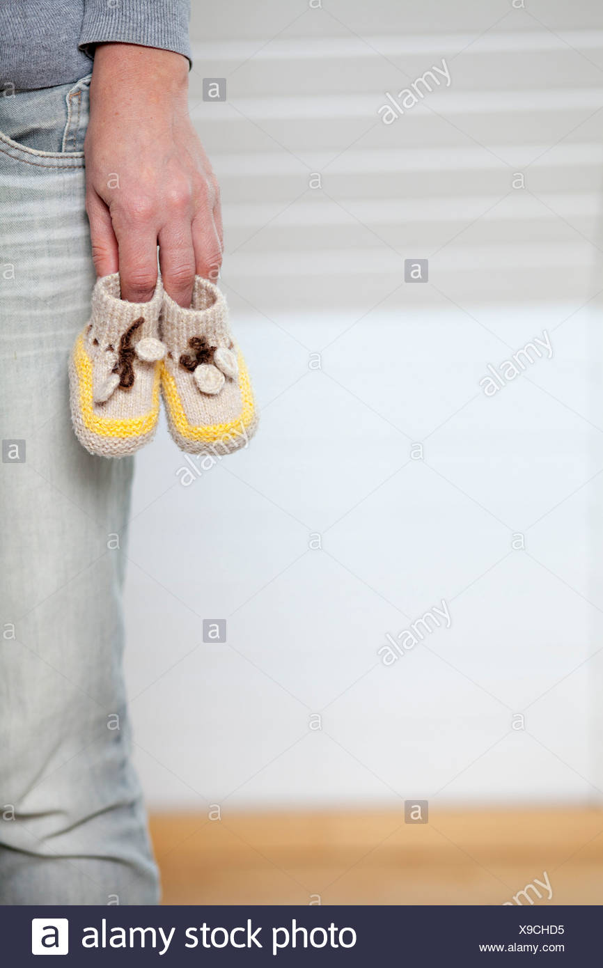 Person Holding Baby Booties, Munich, Bavaria, Germany - Stock Image