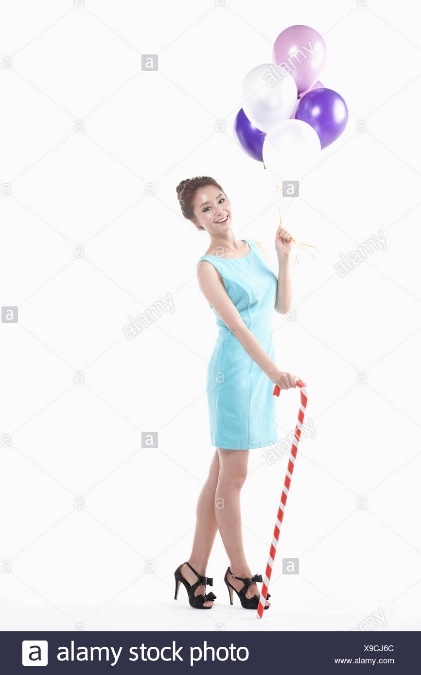 a lady in mini dress posing with balloons and cane stick - Stock Image