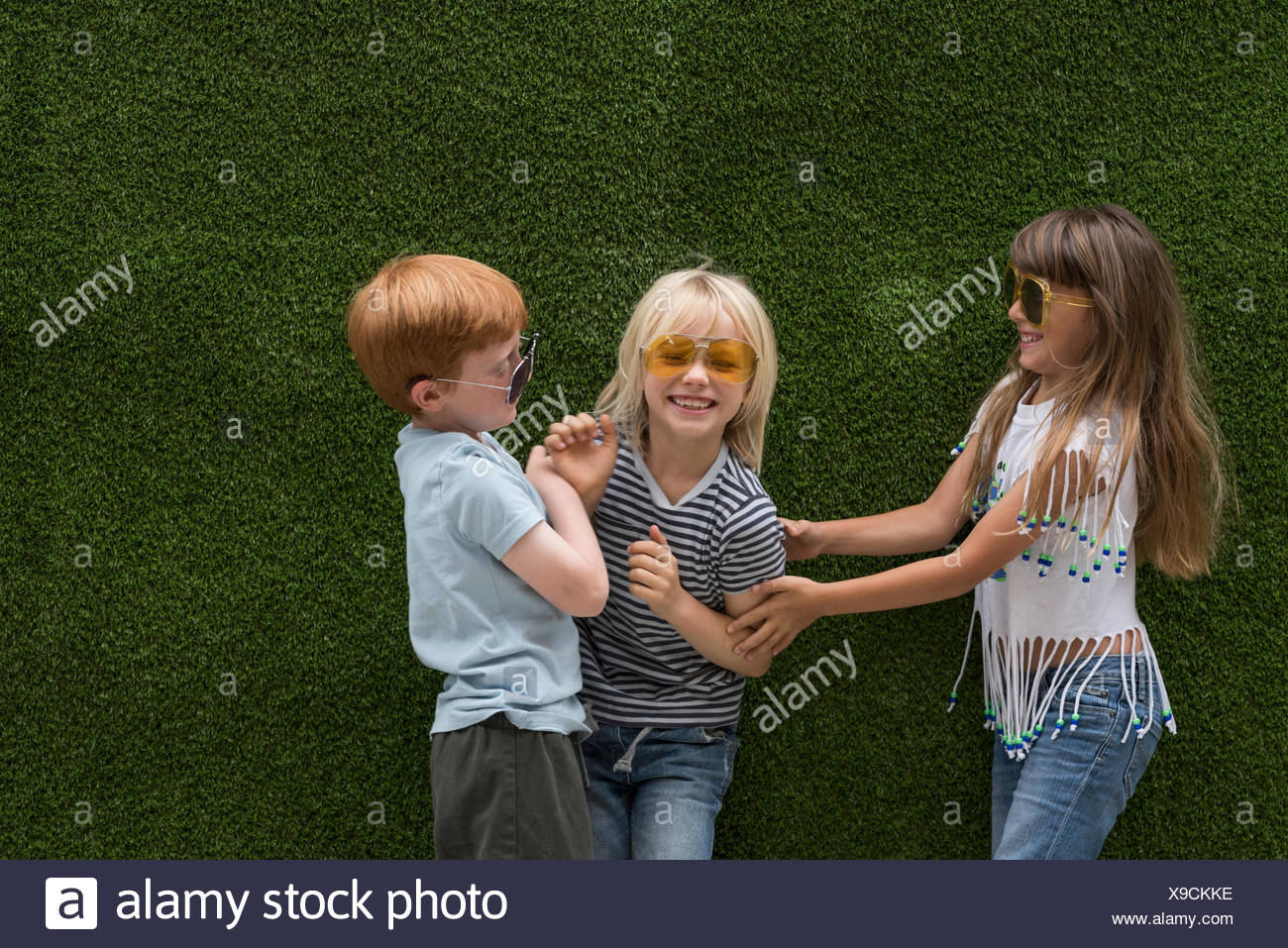Children in front of artificial turf wall playing tickle stock image