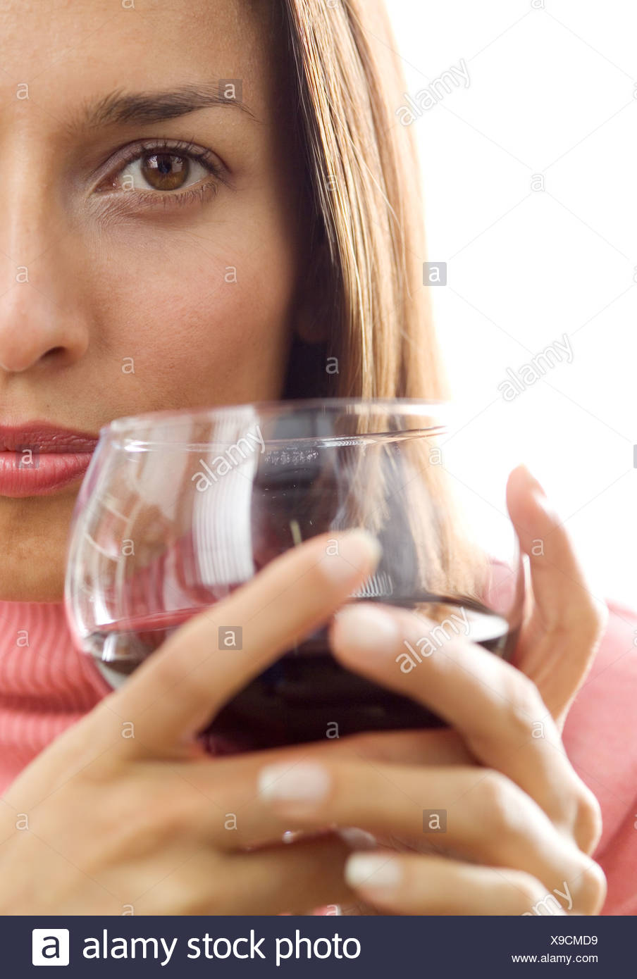 Woman holding a glass of red wine - Stock Image