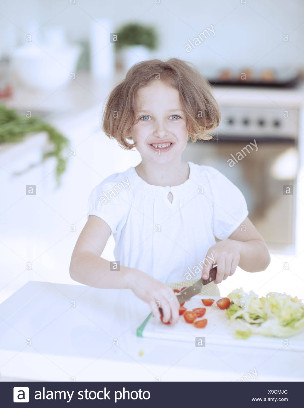 Young girl chopping tomatoes and making a salad in the kitchen - Stock Image