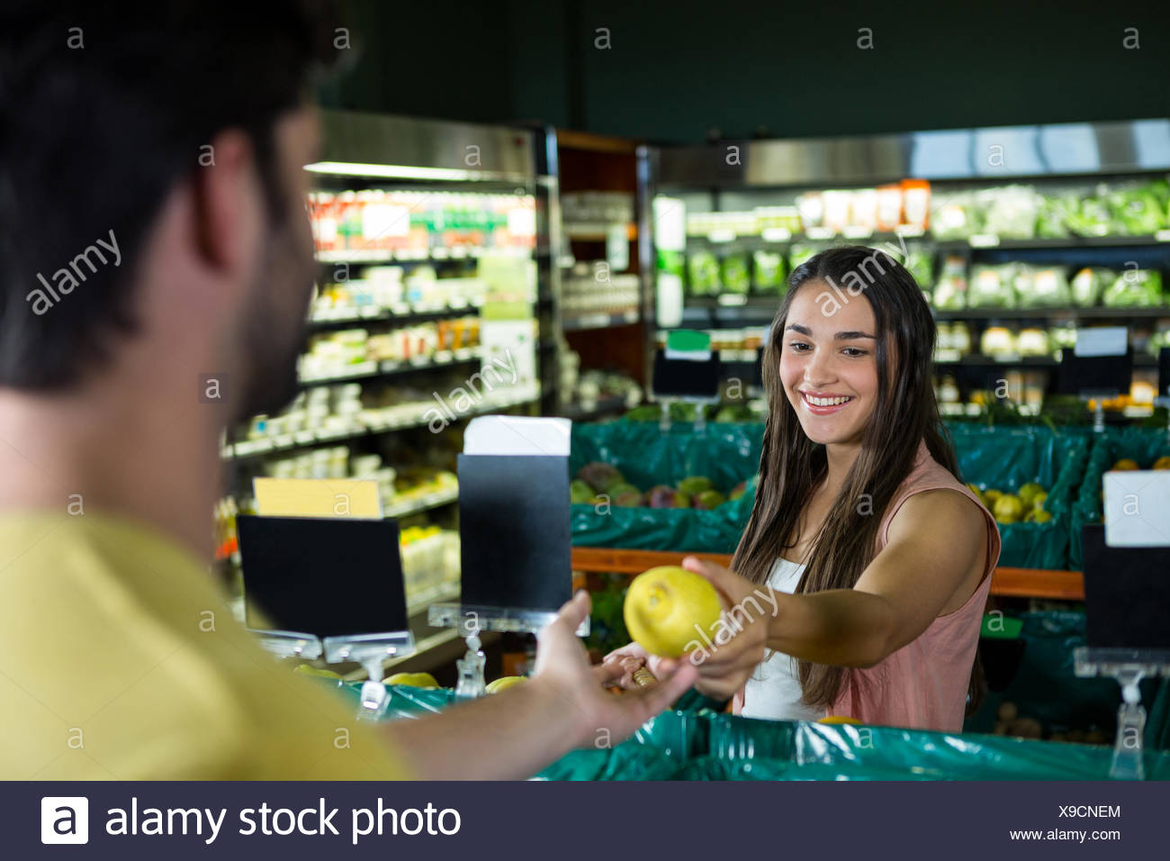 Woman giving fruit to cashier for billing at supermarket - Stock Image