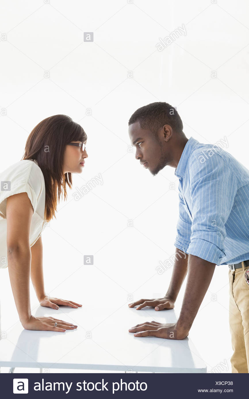 Business teamwork having a stand off at their desk - Stock Image