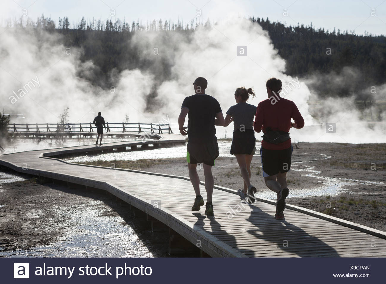 Joggers on a boardwalk through a geyser basin in Yellowstone National Park Wyoming. Stock Photo