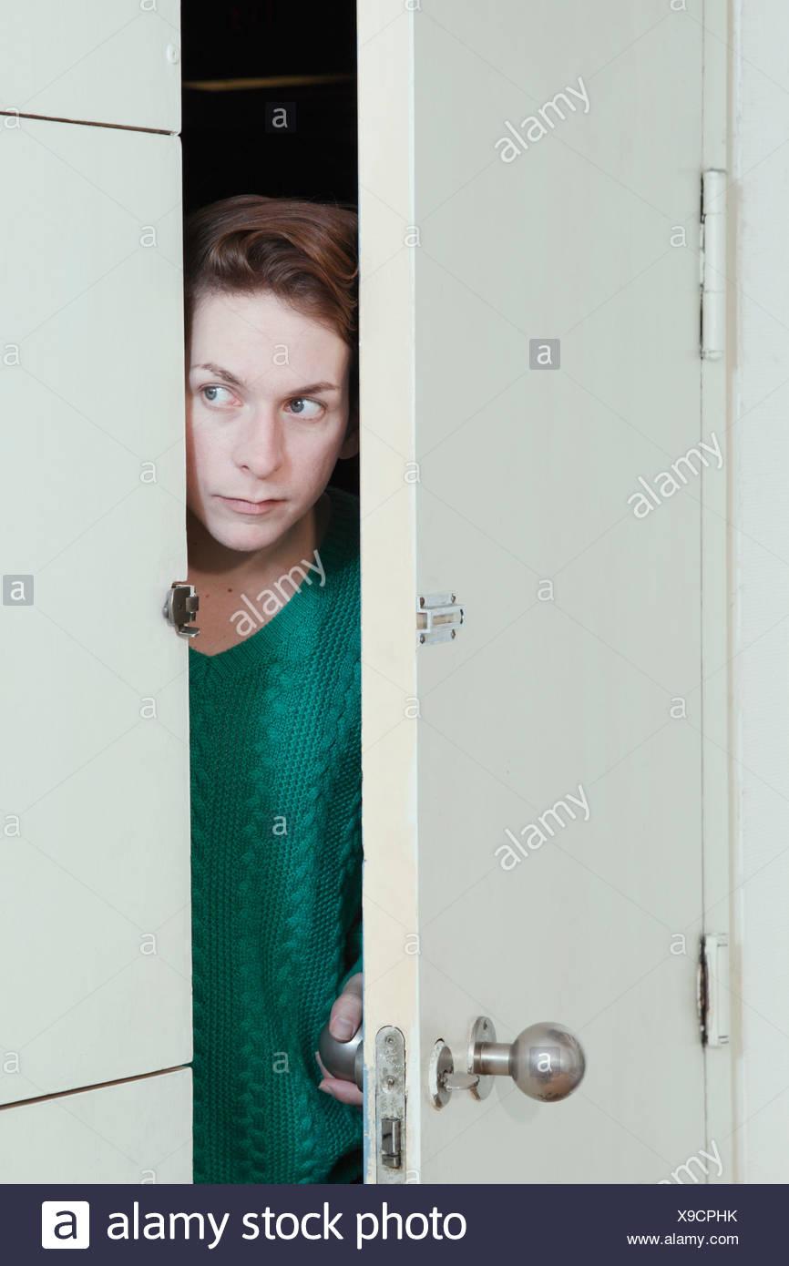 Man peeking through doorway - Stock Image
