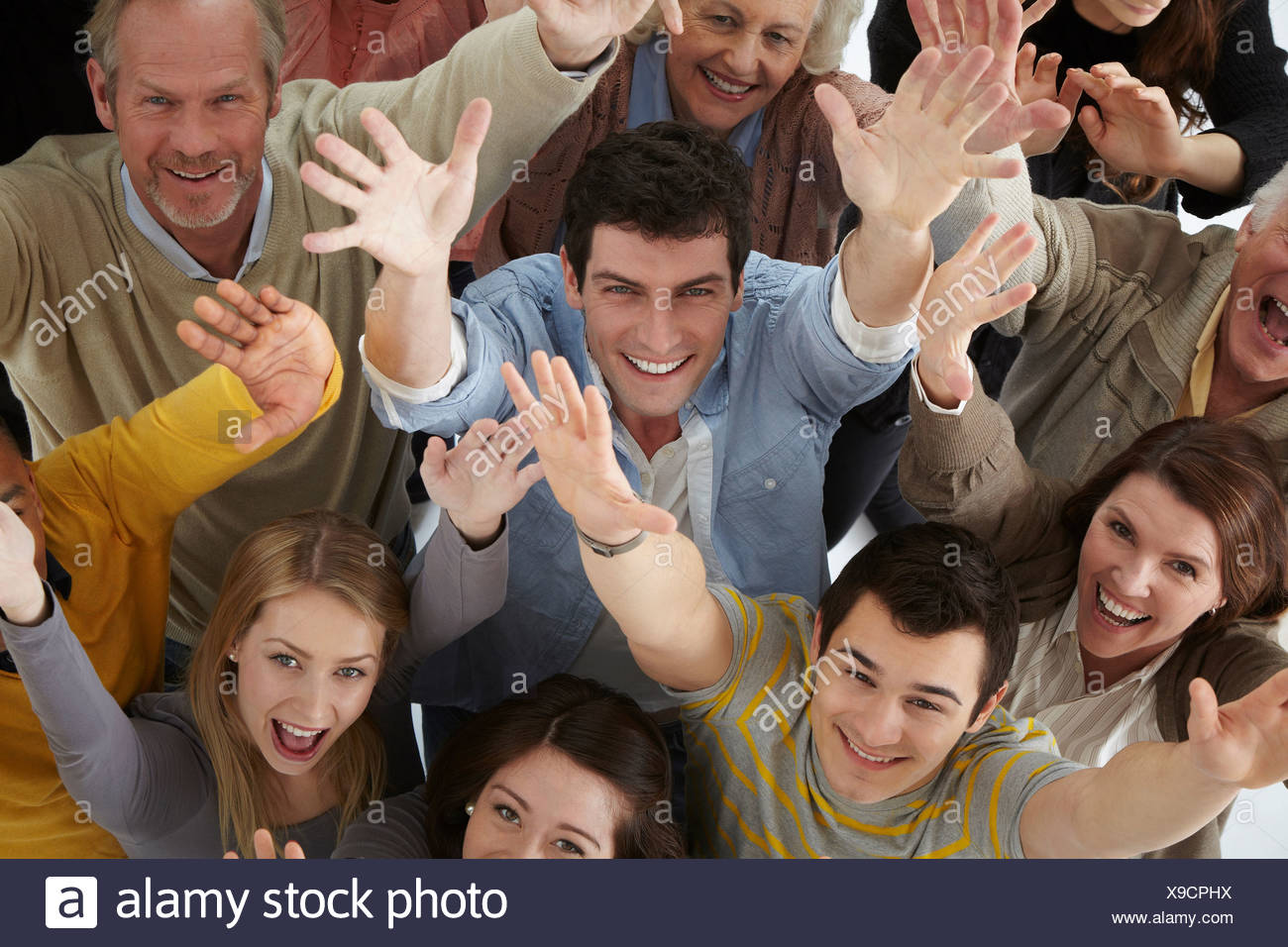 Group of people with arms raised, high angle - Stock Image