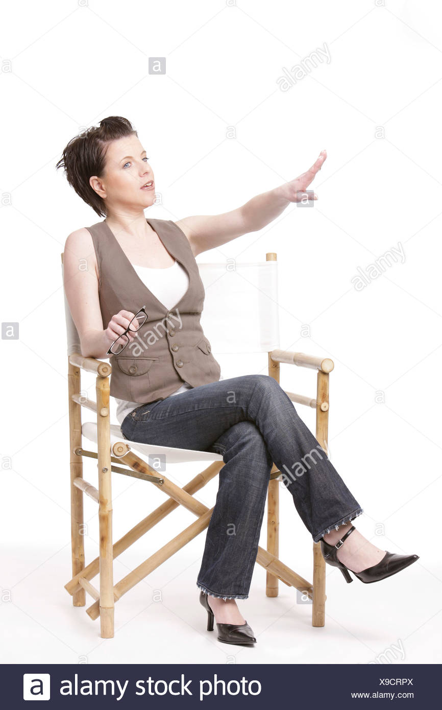 A woman sitting in a director´s chair and giving orders - Stock Image