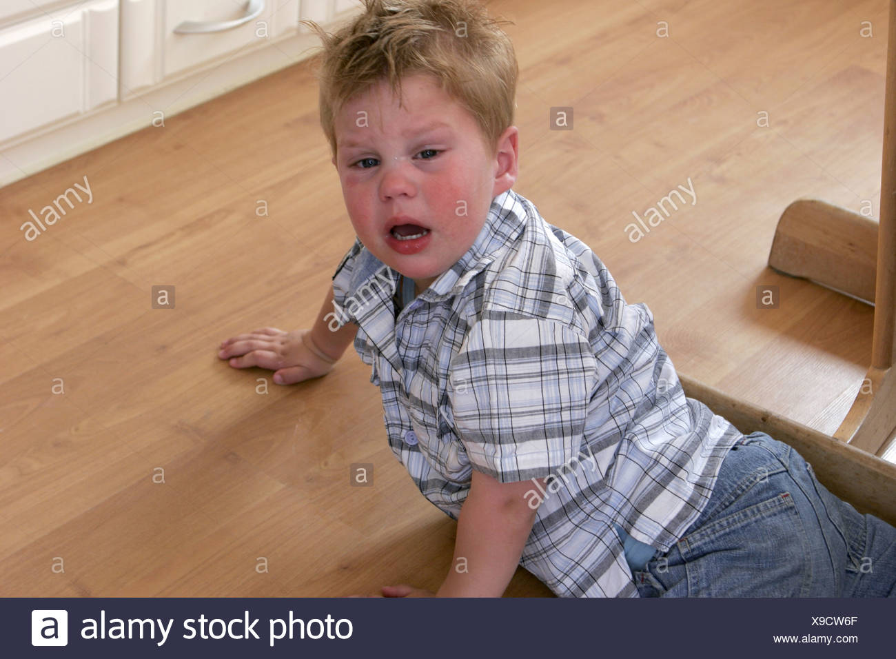 Little boy throwing a tantrum. The toddler child is weaning, whining and sobbing on the floor. - Stock Image