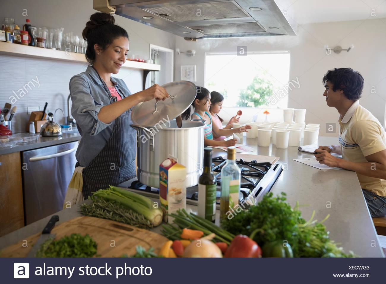 Family preparing vegetable stock in kitchen - Stock Image