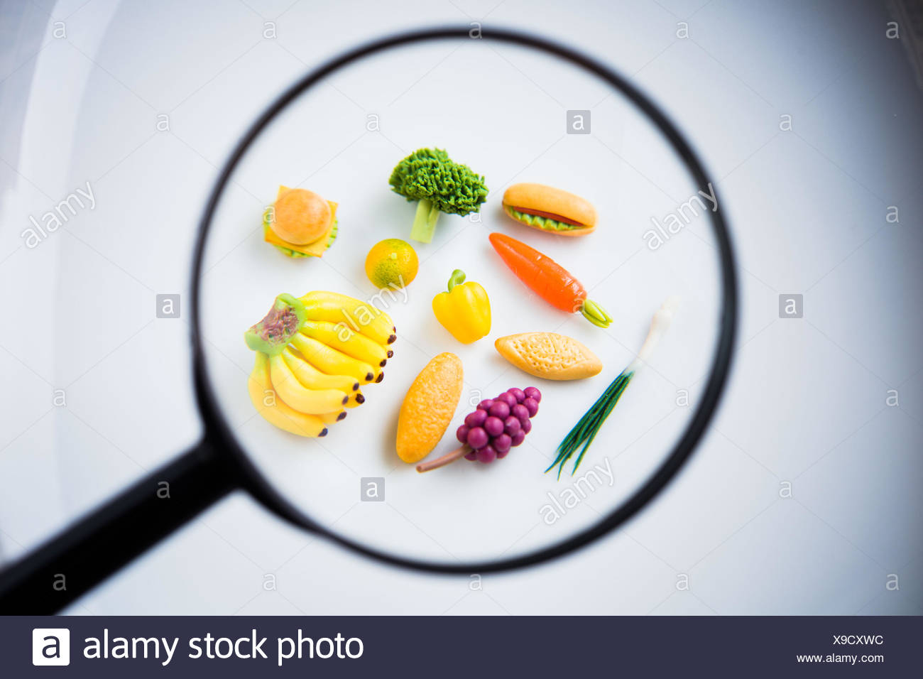 Food and magnifying glass. - Stock Image