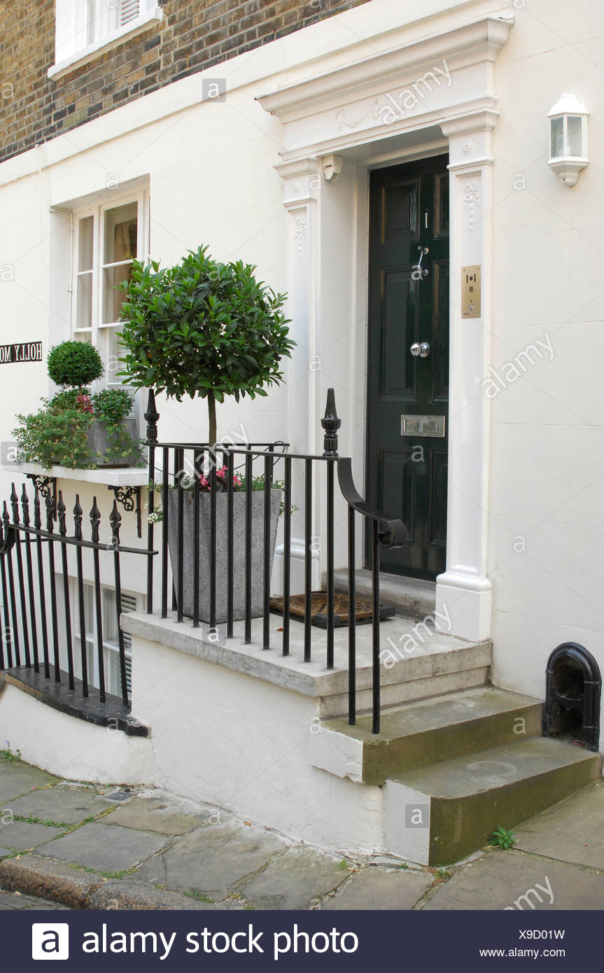 A Traditional Black Front Dowith White Pediment Stone Steps Up To House With Black Railings And Potted Topiary Tree Stock Photo Alamy
