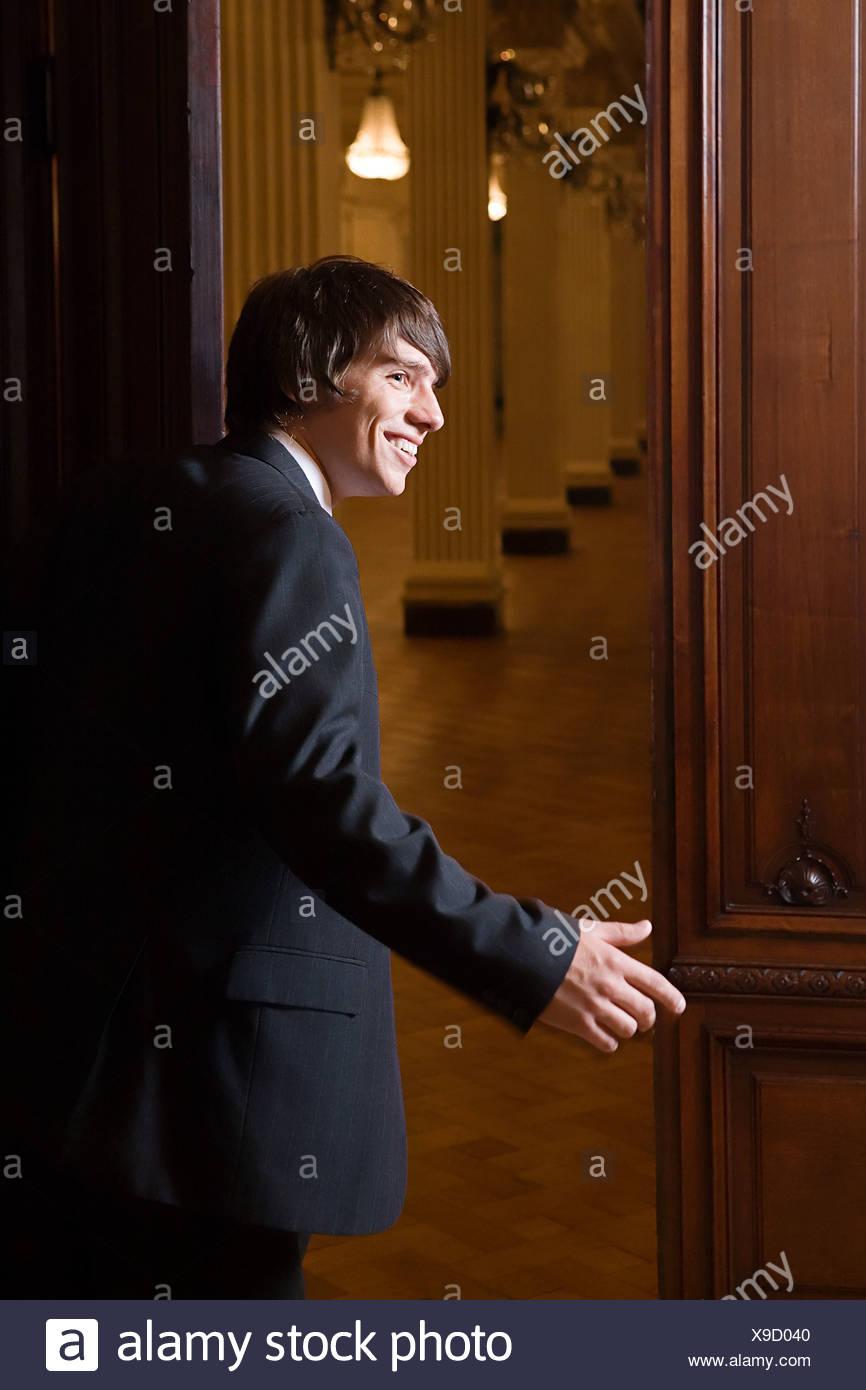 Boy in a suit opening door - Stock Image