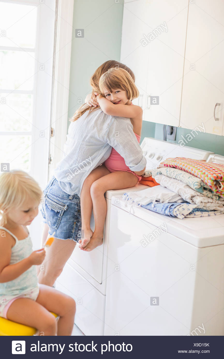 Mother hugging daughter in utility room - Stock Image
