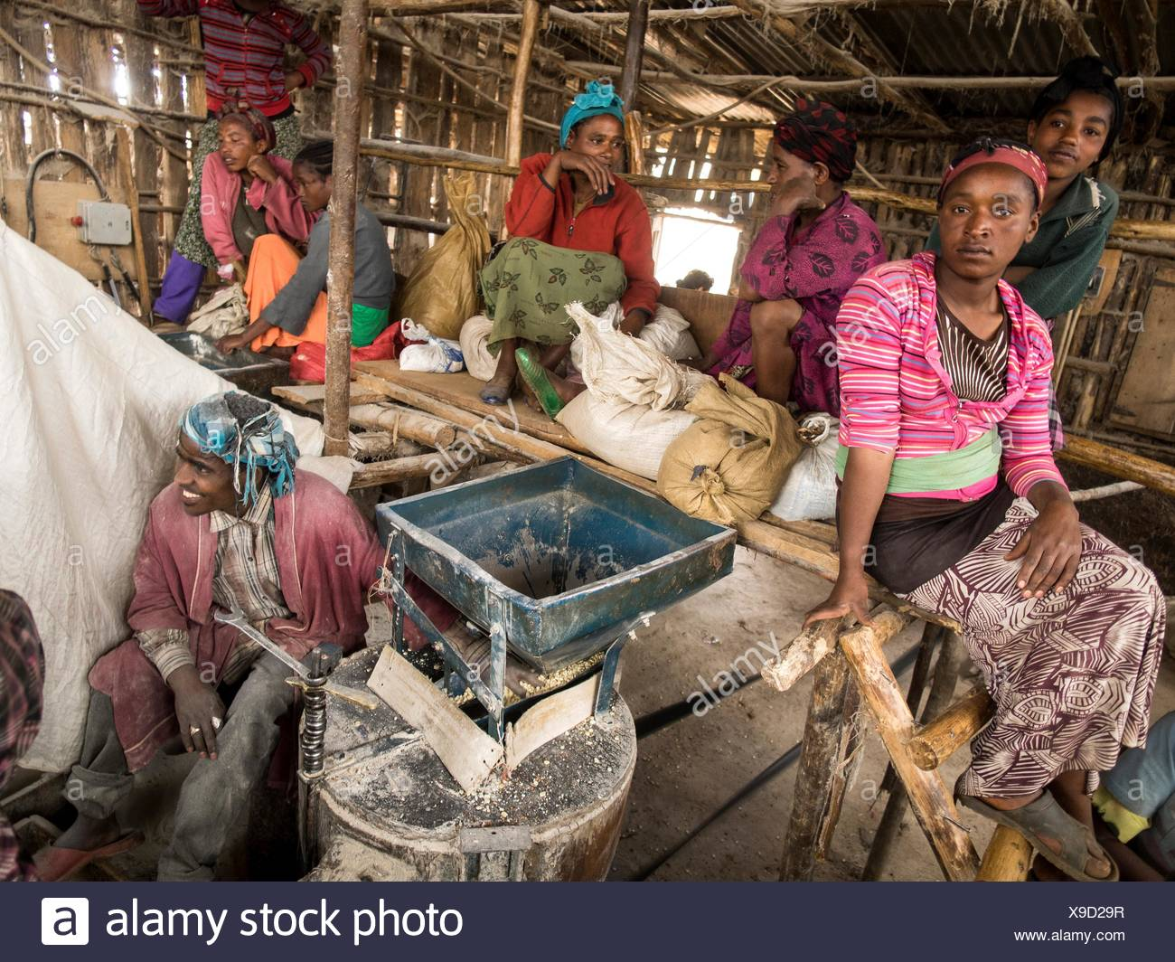 People waiting to grind millet a local mill. - Stock Image