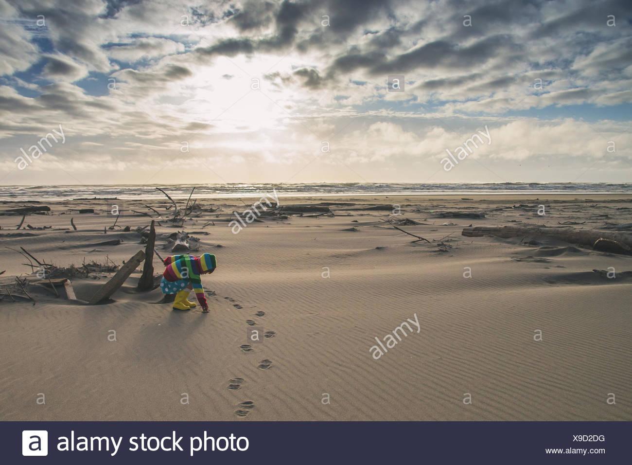 Girl on beach bending down - Stock Image