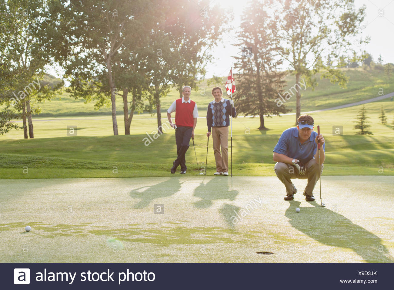 golfer focussed on putt while friends watch Stock Photo