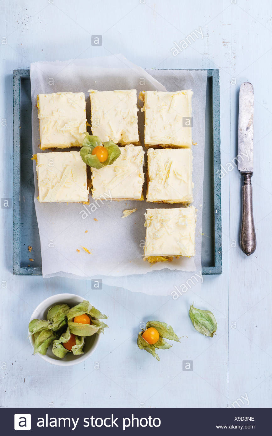 Homemade sliced cake with creamy mousse and tropical fruits mango and physalis served in wooden tray over light blue background. - Stock Image