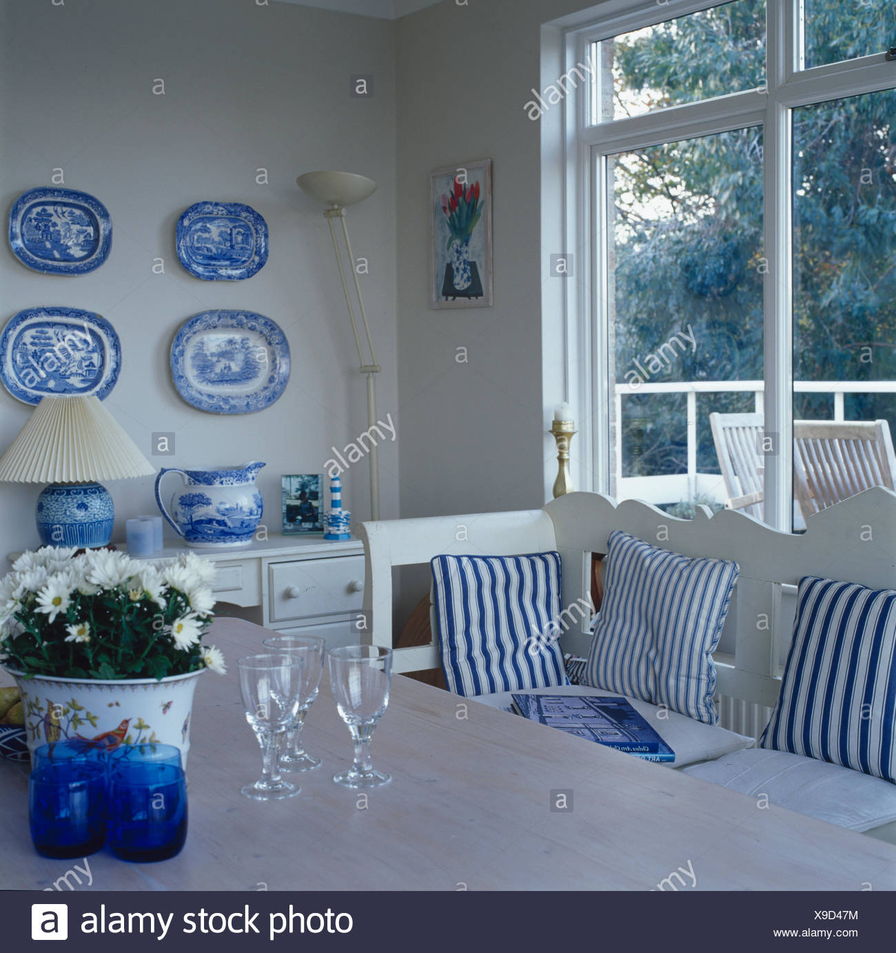 Collection of blue+white plates on wall of dining room with blue striped cushions on white settle in front of window - Stock Image