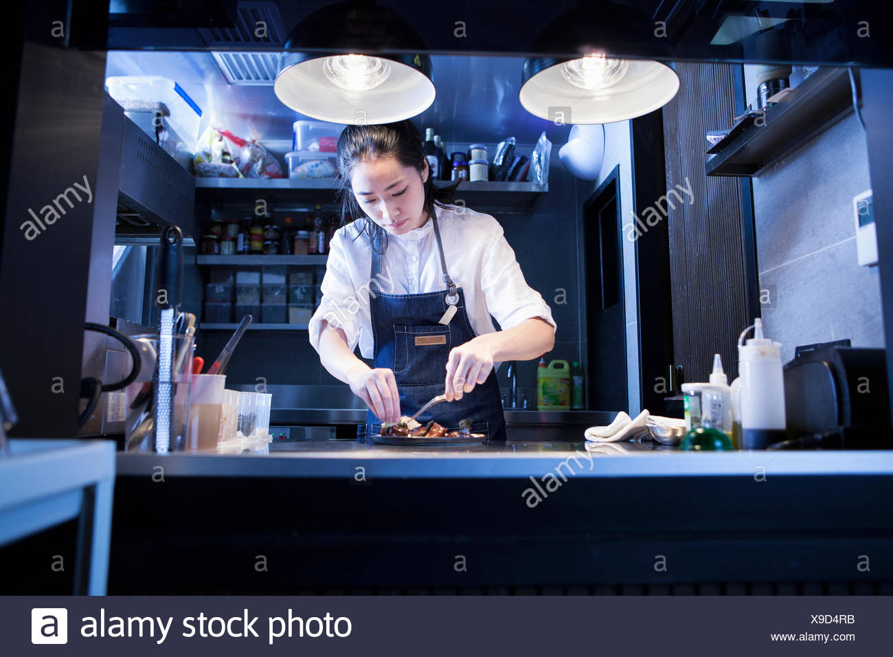 Chef in commercial kitchen preparing food - Stock Image