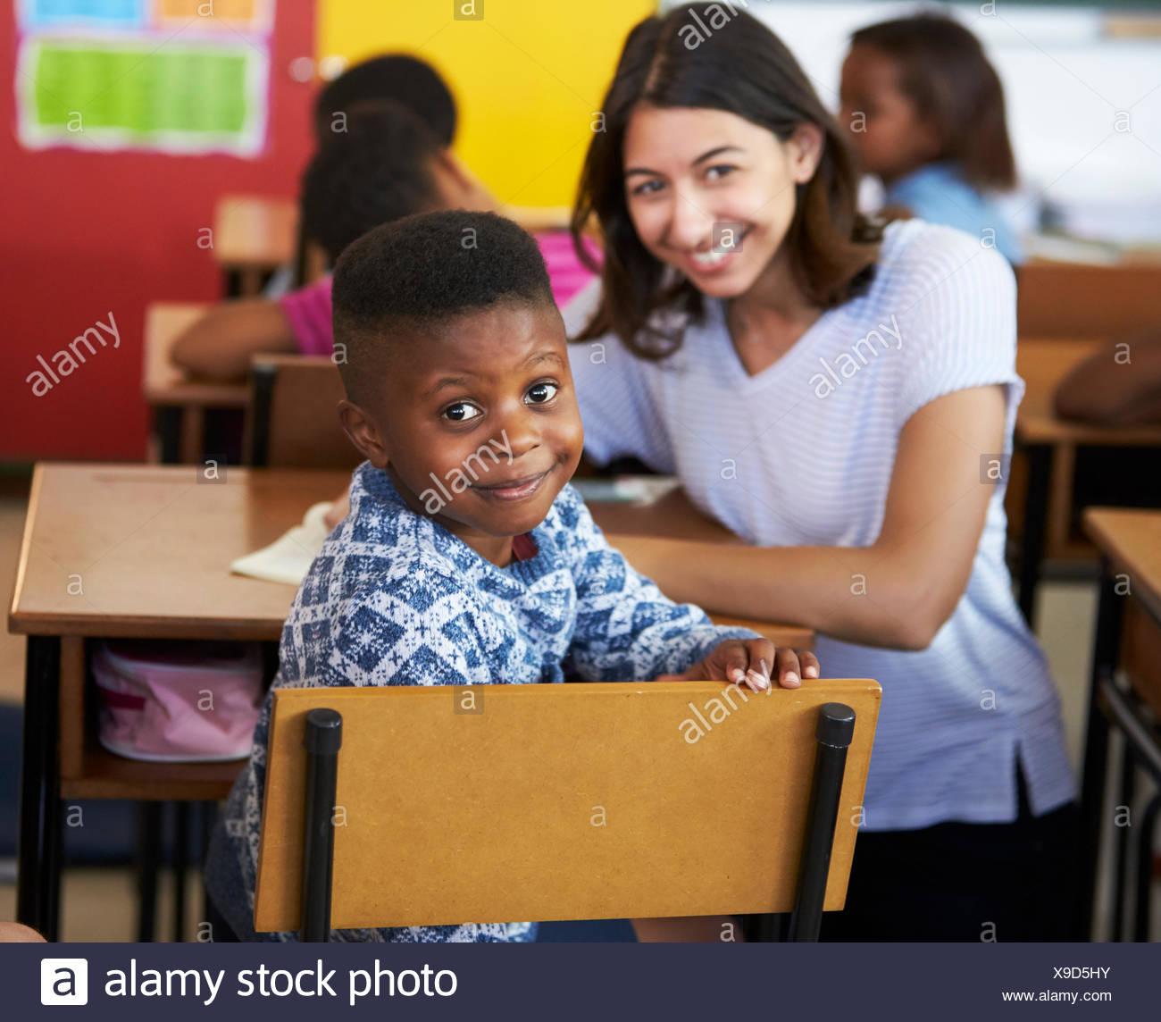 Female Volunteer teacher and elementary school boy smiling to camera - Stock Image