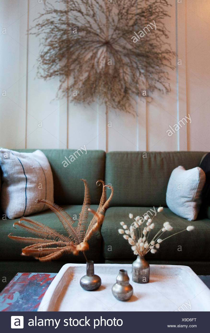 Sitting room with dried flower arrangements on wall and coffee table - Stock Image