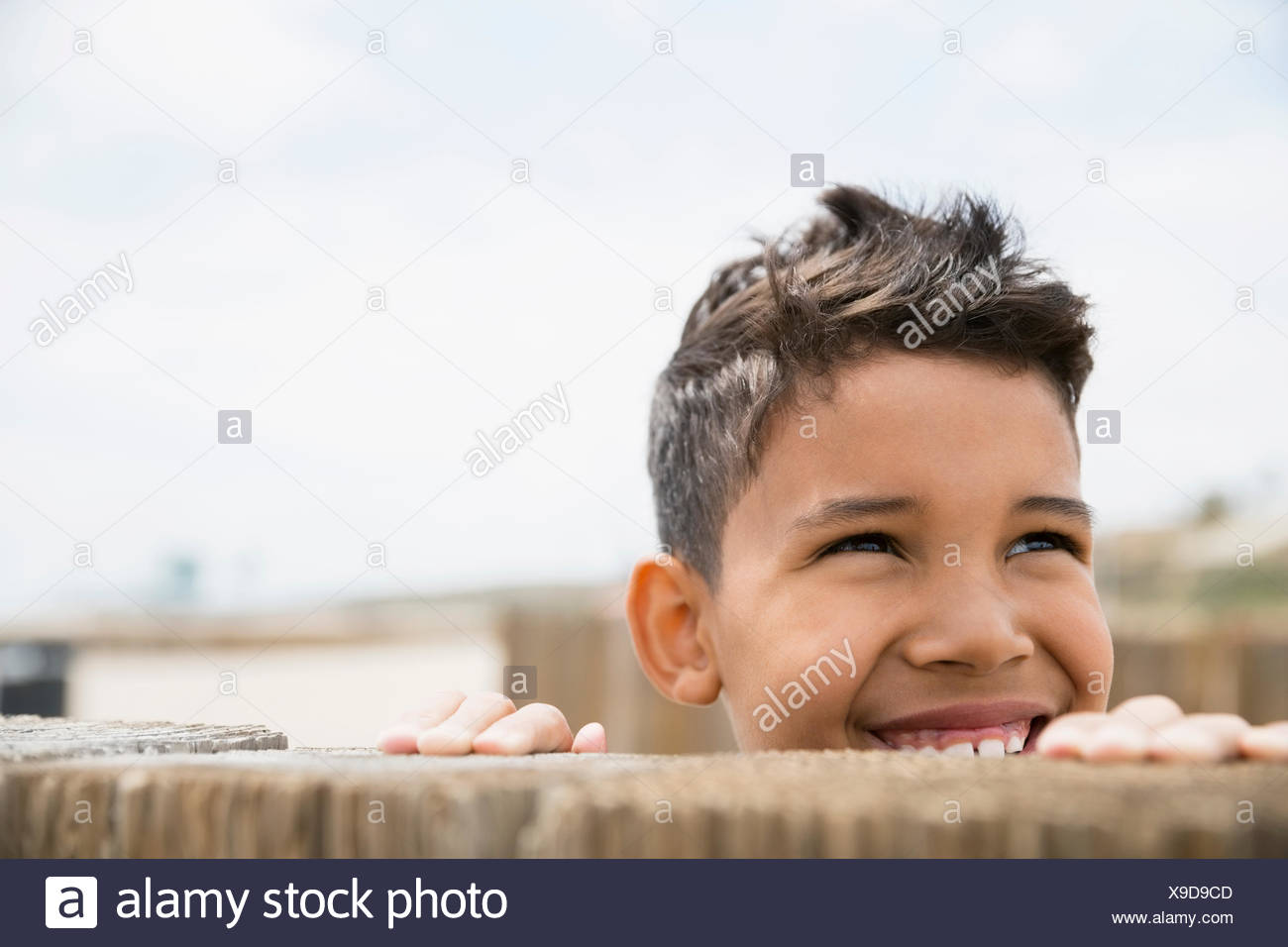 Smiling boy looking up from behind wall - Stock Image