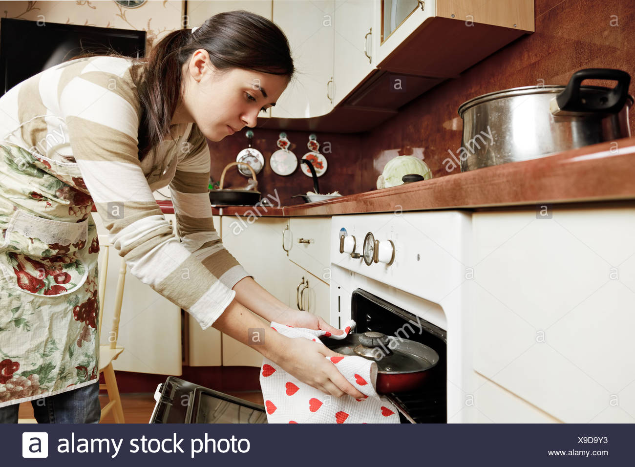 Housewife taking frying pan from oven Stock Photo