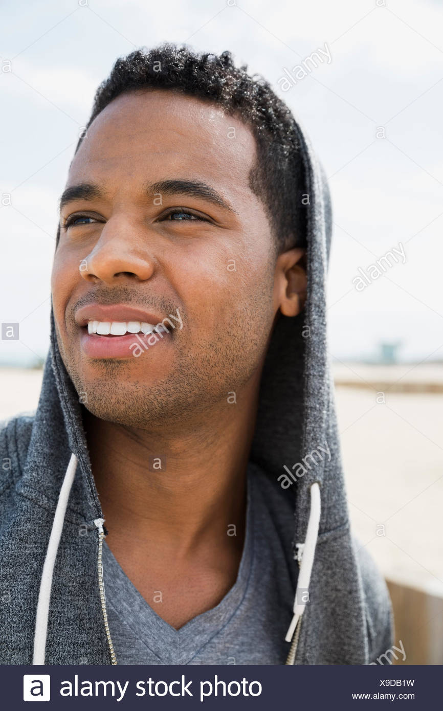 Close up portrait man in hoody looking away - Stock Image