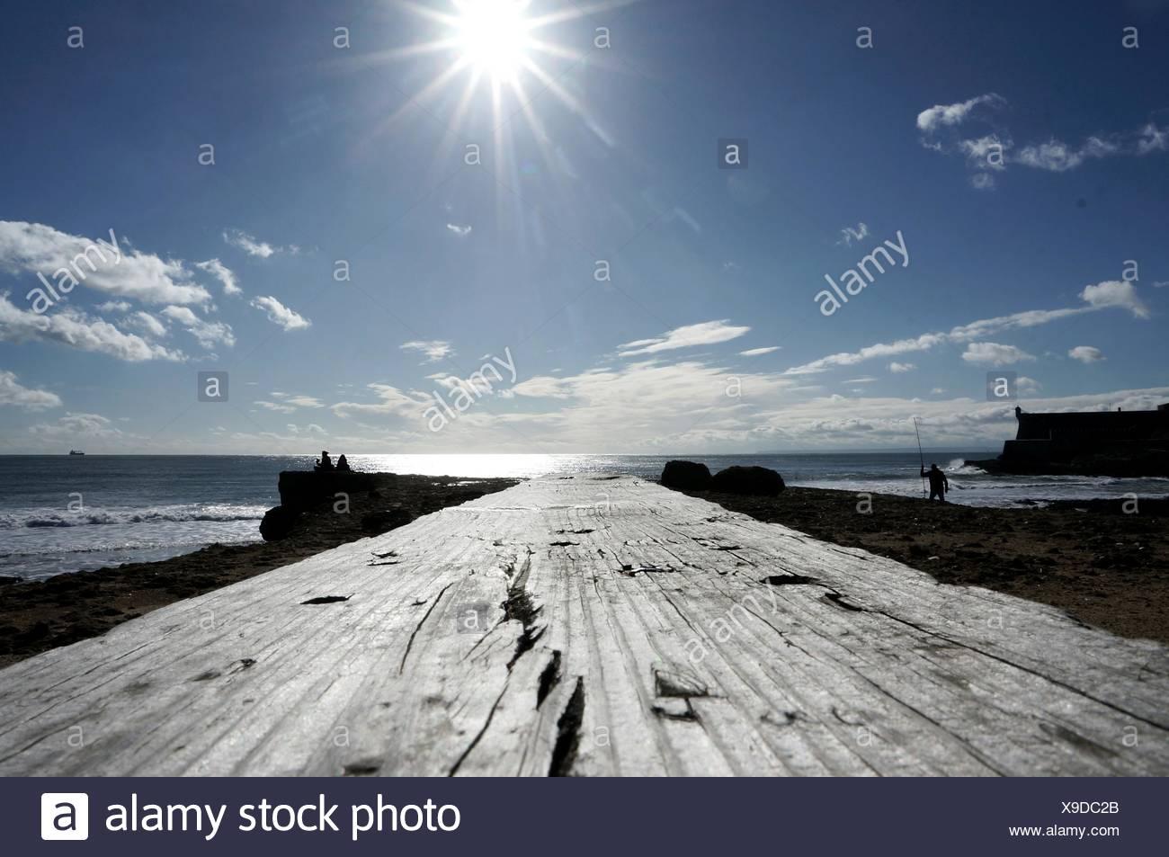 Boardwalk Leading Towards Lake Against Sky On Sunny Day Stock Photo