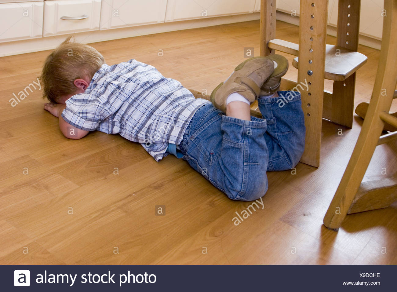 Little child throwing a temper tantrum at home. The toddler is down on the floor, hiding his face, out of control and misbehaving. Stock Photo