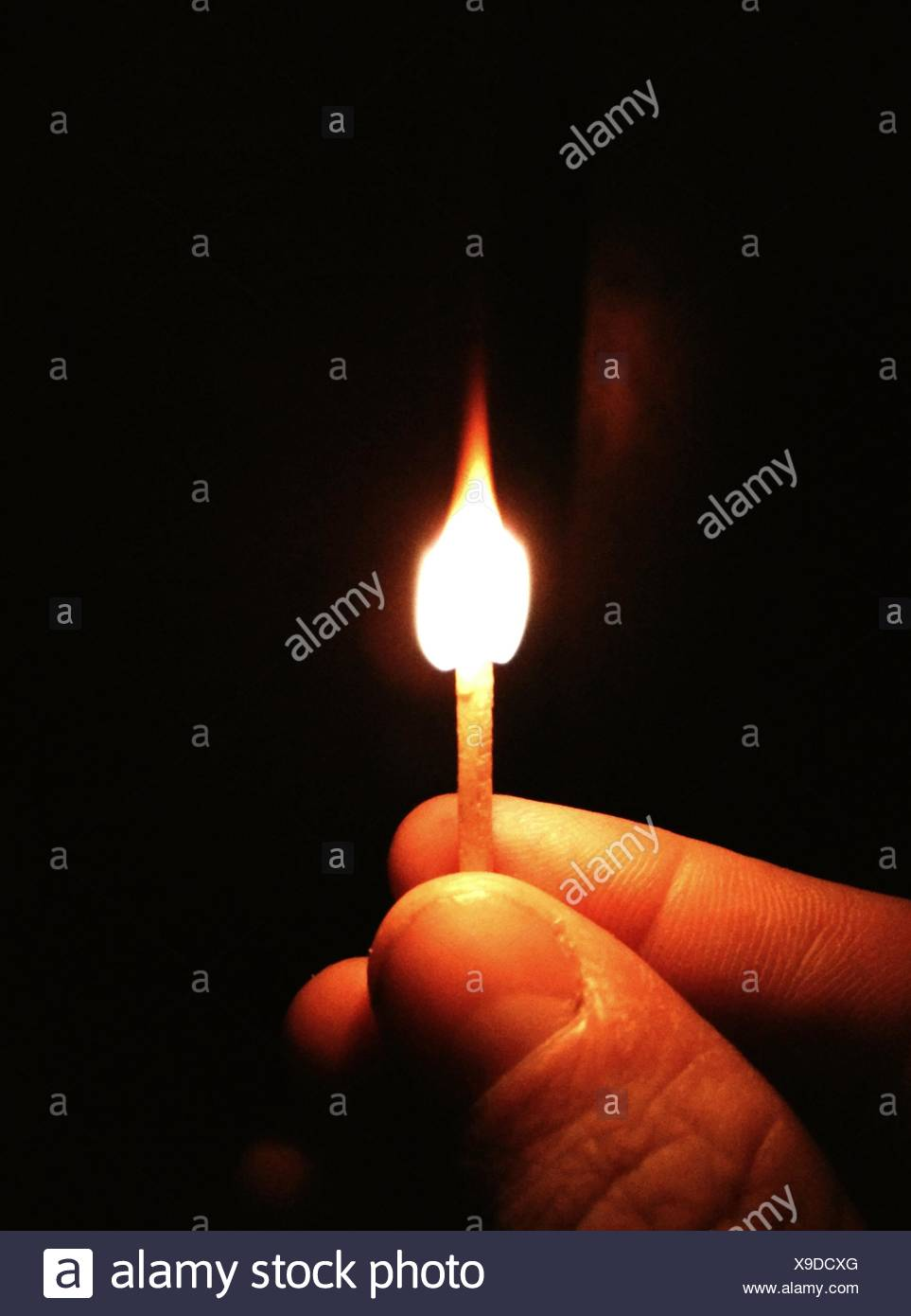 Hand Holding Lit Matchstick - Stock Image