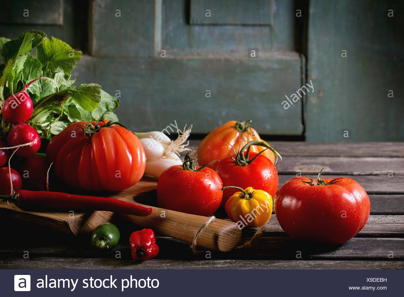 Heap of fresh ripe colorful vegetables tomatoes, chili peppers, green onion and bunch of radish on wooden chopping board over ol - Stock Image