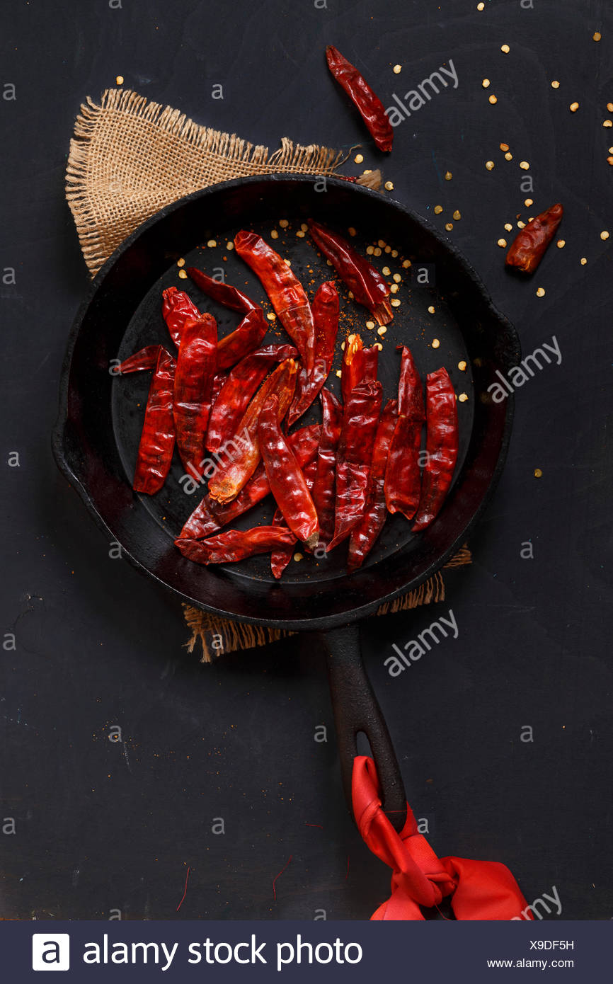 Dried Red Chillies in a cast iron skillet - Stock Image
