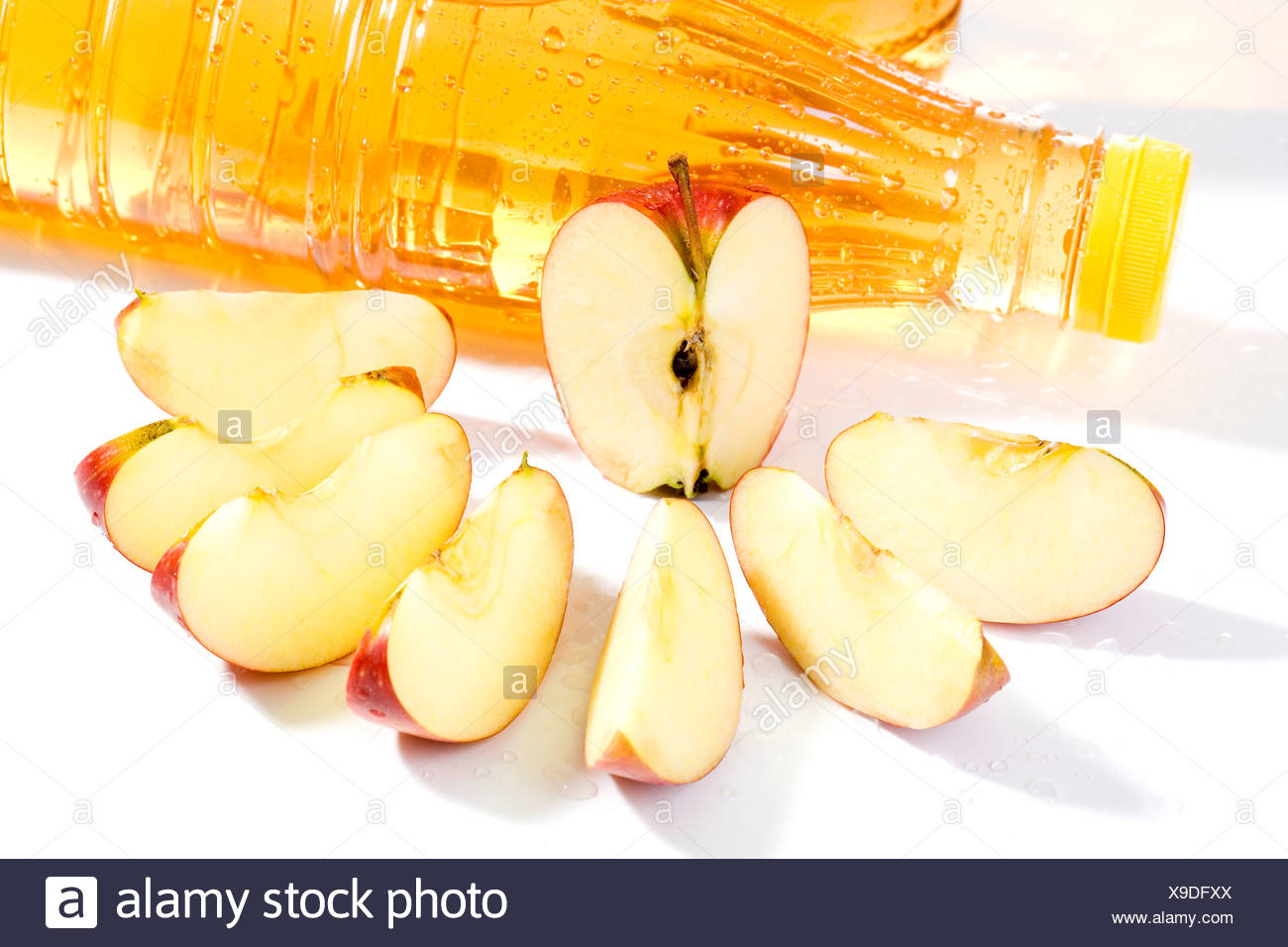 Apple slices and apple juice bottles, close up - Stock Image