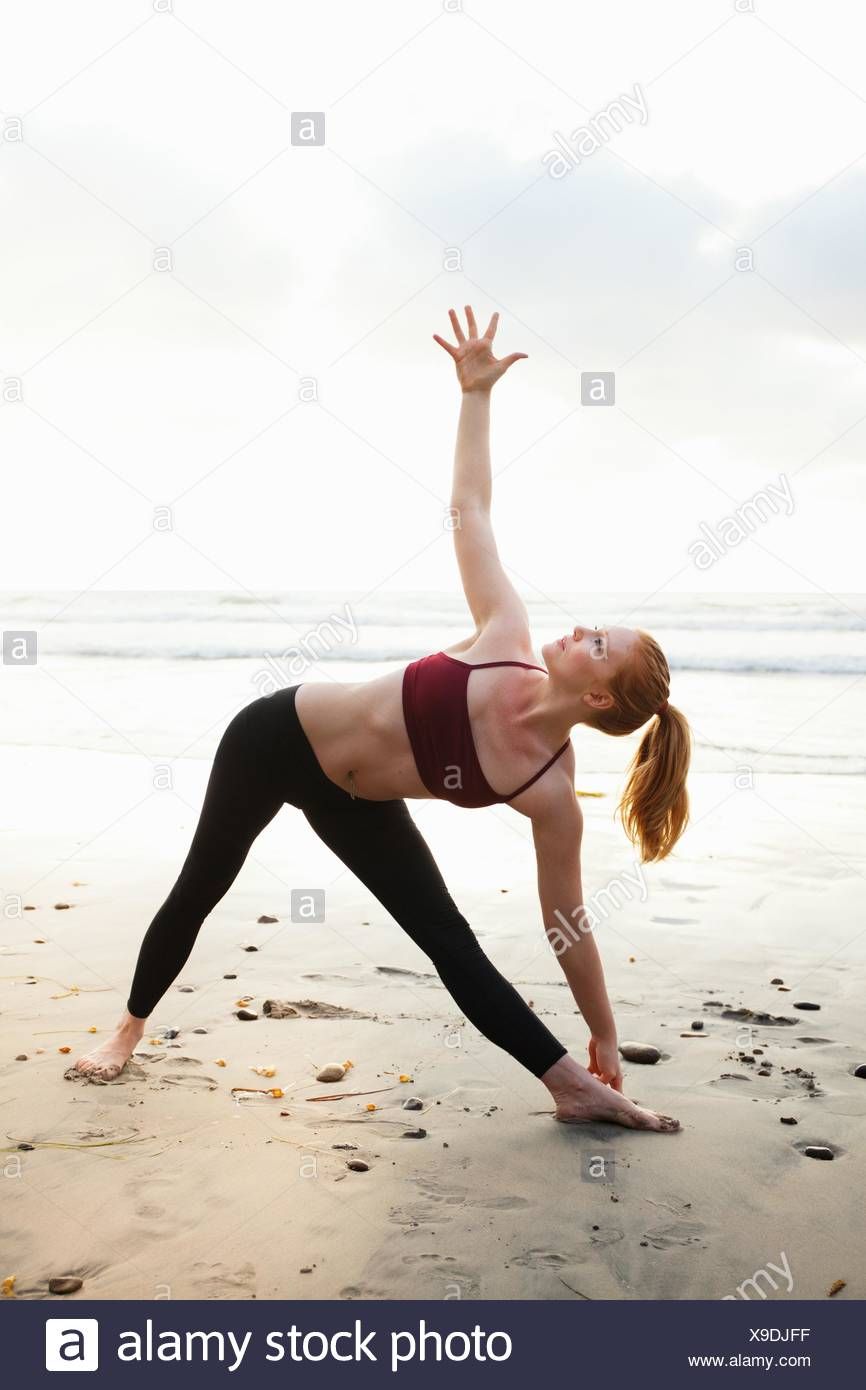 Mid adult woman practicing triangle yoga pose on beach - Stock Image