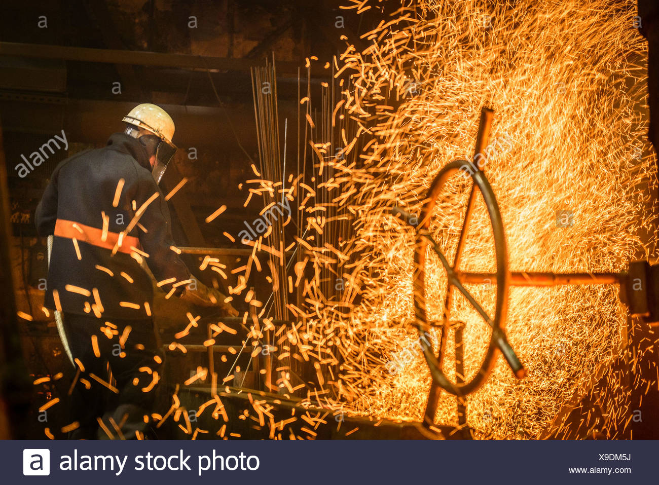 Steel worker amongst sparks in steel foundry - Stock Image