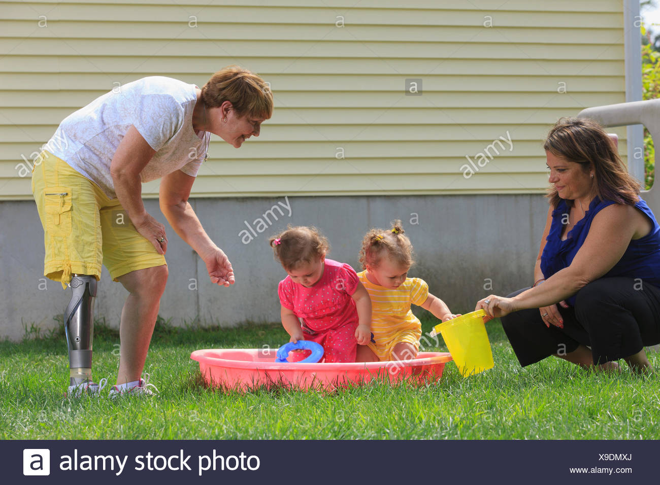 Grandmother with a prosthetic leg playing with her grandchildren on a child's pool - Stock Image