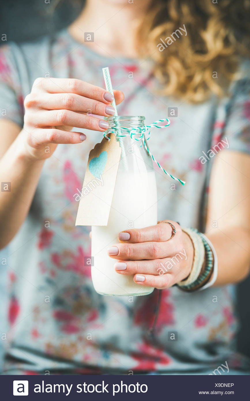 Young woman in grey t-shirt holding bottle of dairy-free almond milk in her hands. Clean eating, vegan, vegetarian, dieting, healthy food concept - Stock Image