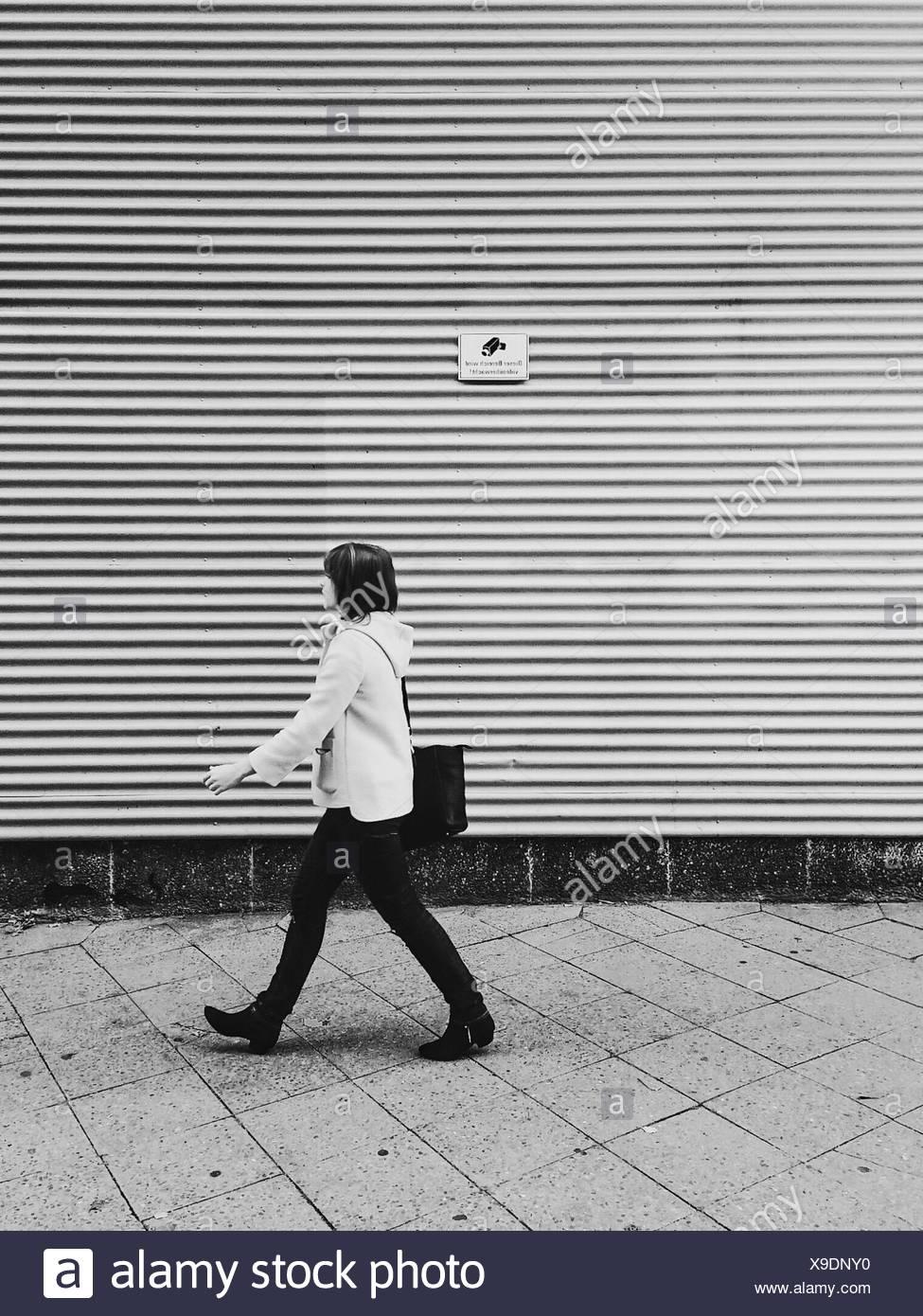Side View Of Woman Walking On Sidewalk Against Shutter - Stock Image