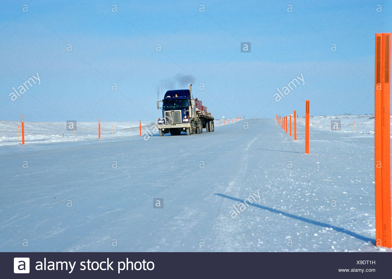 Truck driving on an ice road, built by oil companies and used to connect individual oil drilling sites in winter, Prudhoe Bay - Stock Image